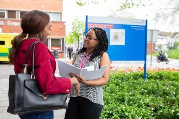 two women talking outside hospital entrance