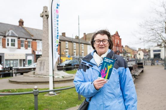 Healthwatch volunteer holding leaflet