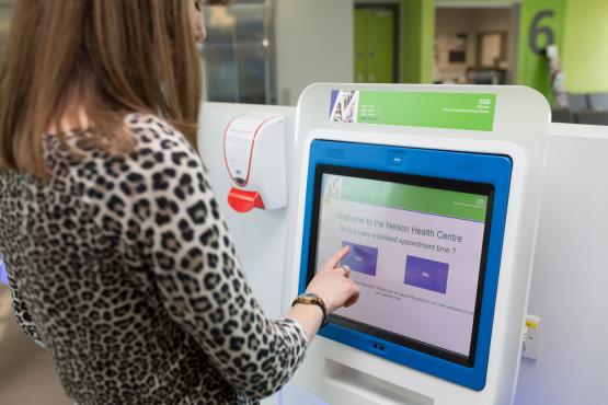 woman at touch screen at gp service