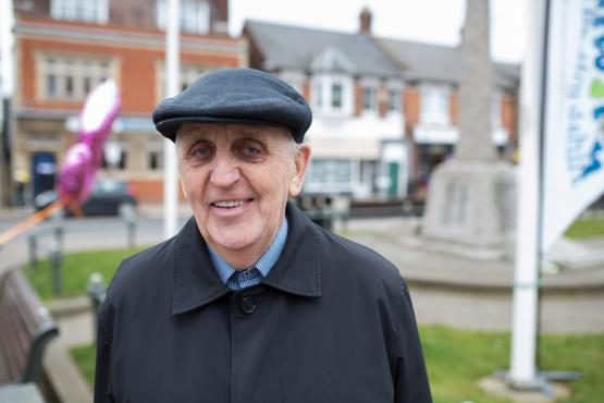 Elderly man wearing a flat hat and coat standing outside