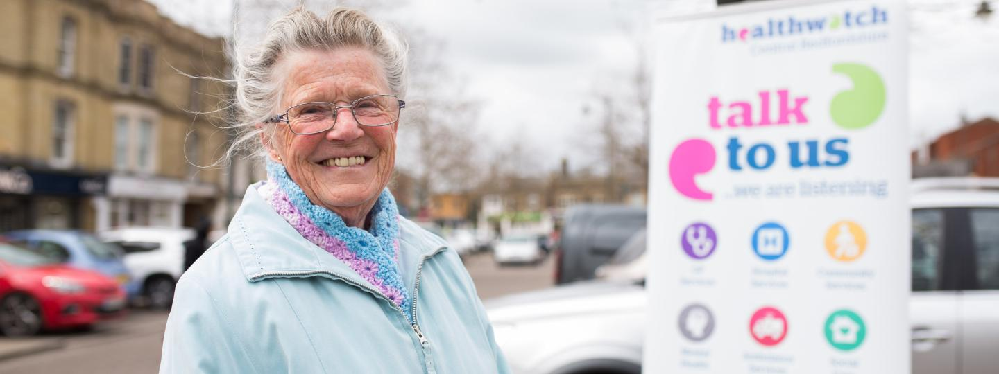 Elderly woman standing in front of a Healthwatch banner