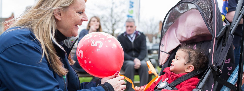 healthwatch volunteer handing balloon to kid